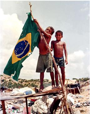 dois-meninos-sem-camisa-em-meio-a-um-ambiente-cheio-de-lixo-erguendo-uma-bandeira-rasgada-do-brasil_01
